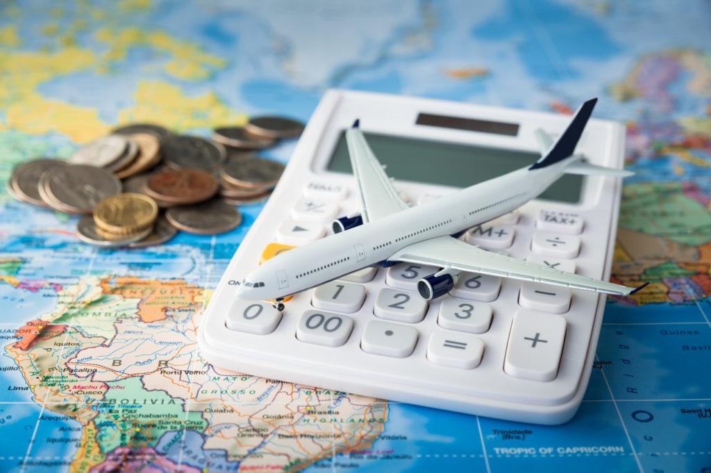Imagem de um avião de brinquedo sob uma calculadora. Ao fundo temos um mapa-mundi e algumas moedas.
